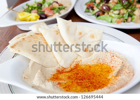 Bowl of hummus with olive oil and paprika. Served with pita bread, and ethnic Egyptian Food in the background - stock photo