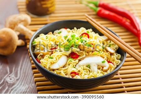 Bowl of instant noodles with shiitake mushrooms, pepper and onion on table, Asian food, top view - stock photo