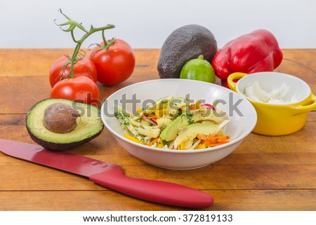 Bowl of Jicama and Mango salad with carrots, cilantro, radish in sweet honey lime dressing on rustic wooden table with white background copy space.