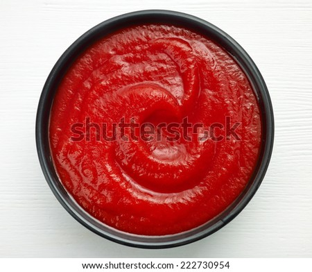 bowl of ketchup or tomato sauce on white wooden table - stock photo
