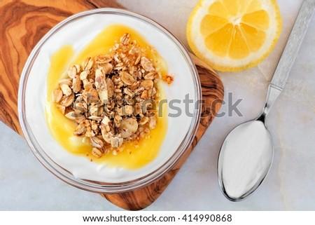 Bowl of lemon flavored yogurt and granola, overhead scene on white marble - stock photo