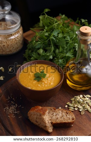 Bowl of lentil and pumpkin soup, bottle of olive oil, piece of bread and green on wooden board - stock photo