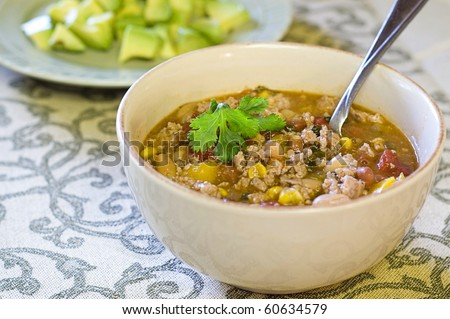 Bowl of Low Calorie White Bean Turkey Chili Topped with Cilantro and Avocado - stock photo