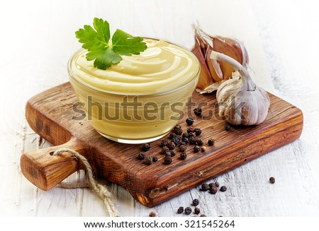 Bowl of Mayonnaise sauce on wooden cutting board - stock photo