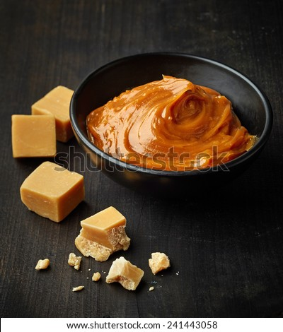 Bowl of melted caramel cream on black wooden table - stock photo
