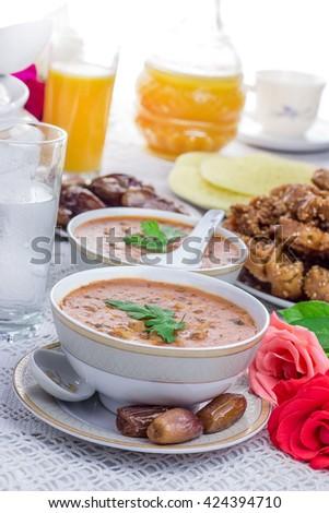 Bowl of Moroccan harira soup,chebakia, dates for iftar - stock photo