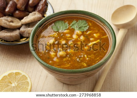 Bowl of Moroccan harira soup, lemon, dates and figs for iftar - stock photo