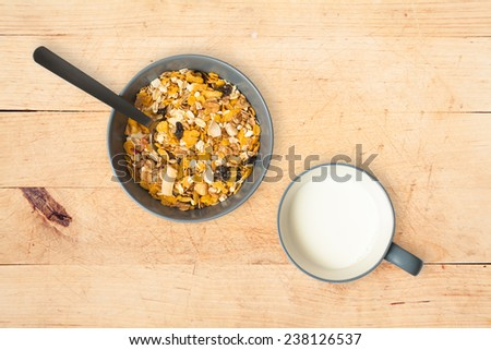 Bowl of muesli and cup of milk. Wood background