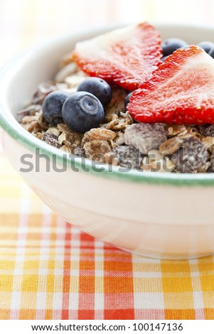 Bowl of muesli, strawberries and blueberries for healthy breakfast