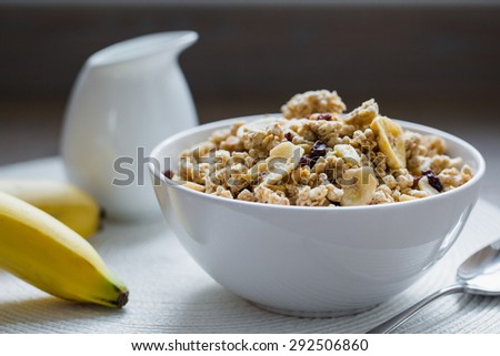 Bowl of muesli with dried banana, spoon, pitcher of milk, fresh banana on white pad. - stock photo