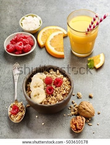 bowl of muesli with fresh berries and banana on grey kitchen table