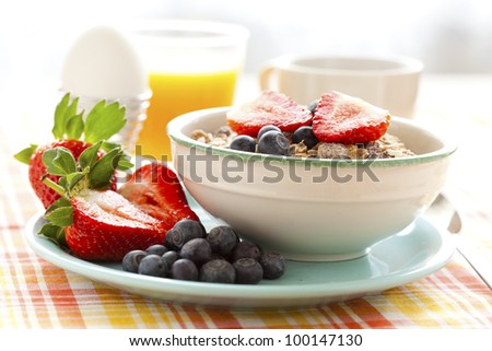 Bowl of muesli with strawberries and blueberries, boiled egg, orange juice and coffee for healthy breakfast - stock photo
