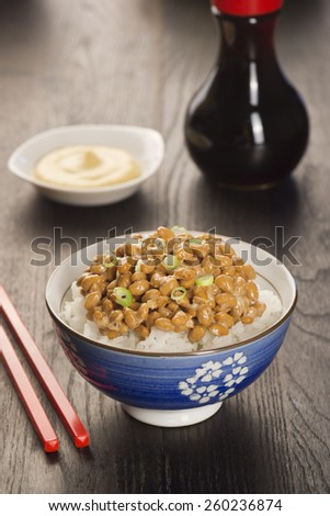 Bowl of Natto, or Japanese Fermented Soybeans, with Sauces in the Background - stock photo