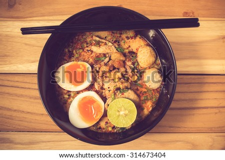 bowl of noodles with vegetables and soft boiled egg on wooden table. delicious noodle. Instant noodle. hot noodle.Homemade Quick Ramen Noodles with egg.vintage color - stock photo