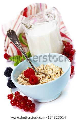 bowl of oat flake, berries and fresh milk on white background - health and diet concept - stock photo