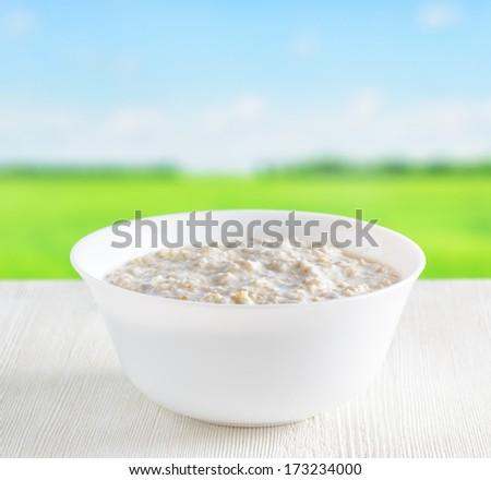 Bowl of oat porridge on nature background. - stock photo