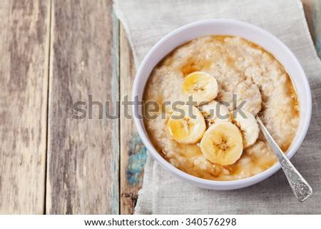 Bowl of oatmeal porridge with banana and caramel sauce on rustic table, hot and healthy breakfast every day, diet food - stock photo