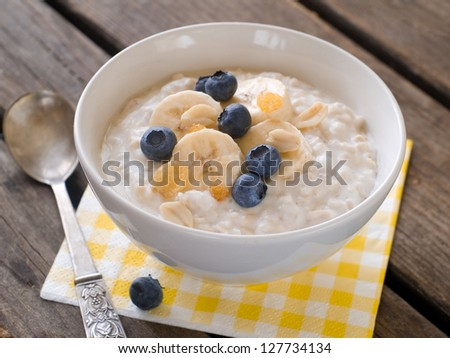 Bowl of oatmeal porridge with bananas and blueberry, selective focus - stock photo