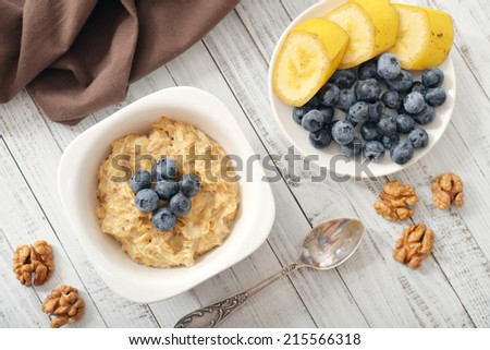 Bowl of oatmeal porridge with bananas and blueberry. Top view. - stock photo