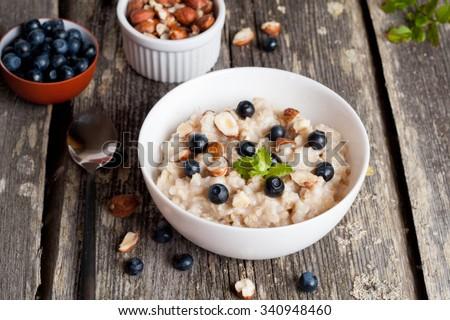 Bowl of oatmeal porridge with blueberry, close up, horizontal - stock photo