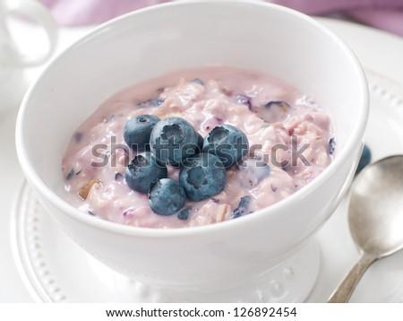 Bowl of oatmeal porridge with blueberry, selective focus - stock photo