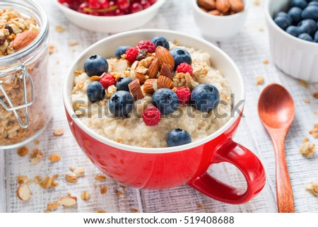 Bowl of oatmeal porridge with fresh blueberries, raspberries, almonds and muesli on white vintage table. Close up. Healthy food, healthy breakfast, healthy lifestyle concept