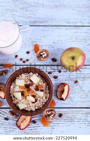 Bowl of oatmeal, walnuts, dried apricots, apples and yogurt on blue wooden background - stock photo