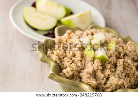 Bowl of oatmeal with chopped apples on top
