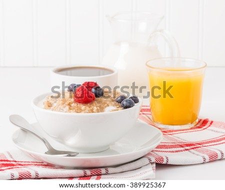 Bowl of oatmeal with fresh berries with coffee and orange juice.