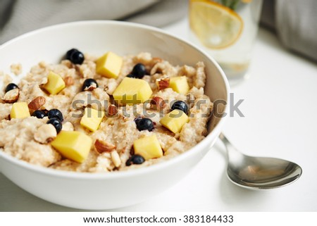 bowl of oatmeal with mango and berries. selective focus