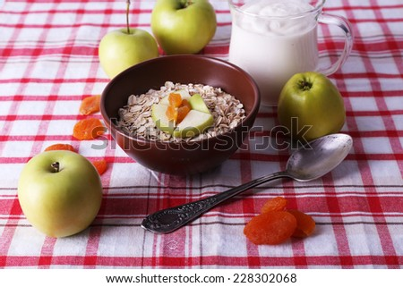 Bowl of oatmeal, yogurt and apples on checkered fabric background - stock photo