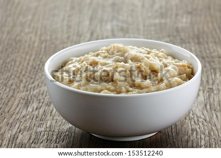 Bowl of oats porridge on wooden table. Healthy breakfast - stock photo