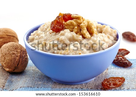 Bowl of oats porridge with raisins and nuts. Healthy breakfast - stock photo