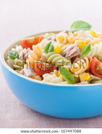 bowl of pasta salad with tuna, tomatoes, sweet corn and basil - stock photo
