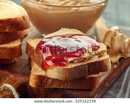 Bowl of peanut butter and peanut butter strawberry jelly sandwich on wooden cutting board. Close-up.