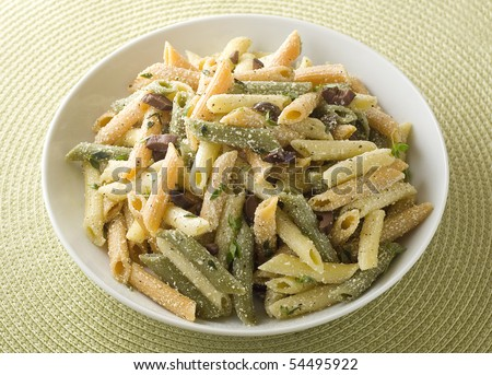 Bowl of penne pasta with fresh herbs, black olives and Parmesan. - stock photo