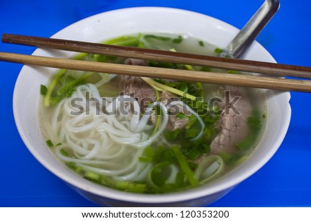 Bowl of Pho Bo, Vietnamese national soup, in street restaurant in Hanoi - stock photo