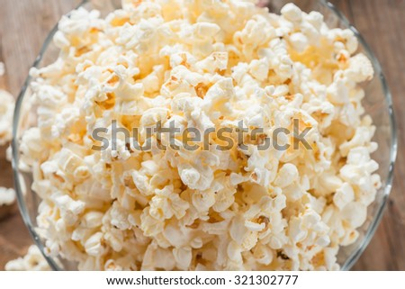 Bowl of popcorn on wood table. Top view.