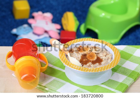 Bowl of porridge for baby and toys  on table, on toys background - stock photo