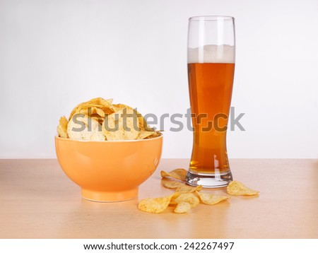 bowl of potato chips or crisps and a glass of wheat beer