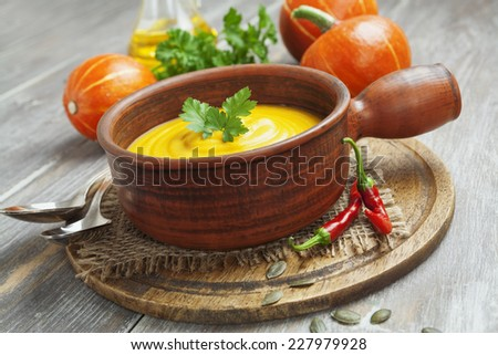 Bowl of pumpkin soup on a wooden table - stock photo