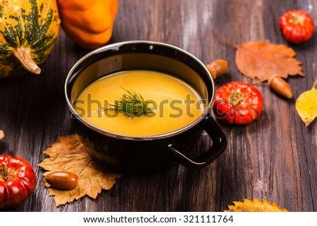 Bowl of pumpkin soup over wooden background. Autumn or halloween concept. Rustic style. Selective focus - stock photo