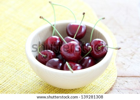 Bowl of red cherries on a yellow cloth and wooden table