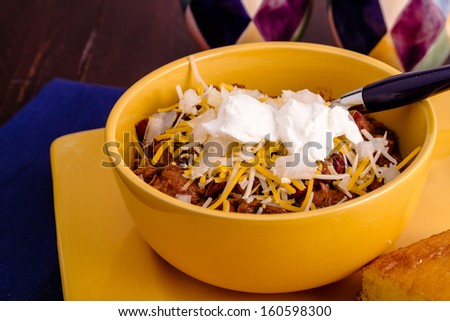 Bowl of red meat chili with toppings and cornbread on yellow plate with blue spoon - stock photo