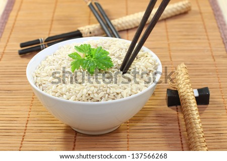 Bowl of rice and chopsticks - stock photo
