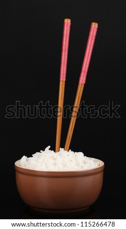 Bowl of rice and chopsticks isoalted on black - stock photo