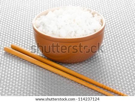 Bowl of rice and chopsticks on grey mat - stock photo