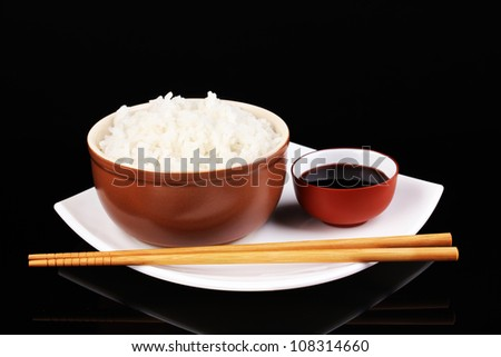 Bowl of rice and chopsticks on plate isolated on black