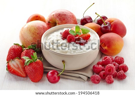 Bowl of rice flakes porridge with various fruits and berries. Healthy breakfast - stock photo