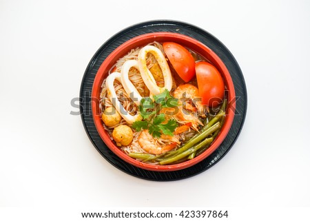 Bowl of rice noodles with cuttle, shrimp and tomatoes isolated on white background - stock photo